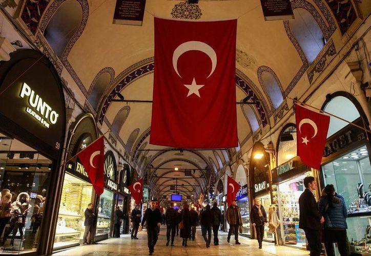 Banderas de Turquía decoran el Gran Bazar de Estambul, el 5 de junio de 2017. El gobierno turco ordenó hoy el arresto de 38 empresarios, presuntamente implicados en el fallido golpe de Estado del pasado mes de julio. (AP/Emrah Gurel)