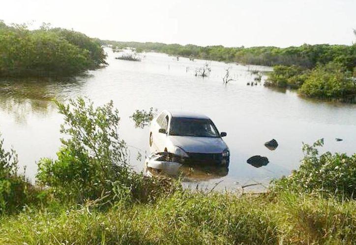 El vehículo del exalcalde de Cansahcab, Paulino Ek, cayó y se hundió en la ciénaga. (Milenio Novedades)