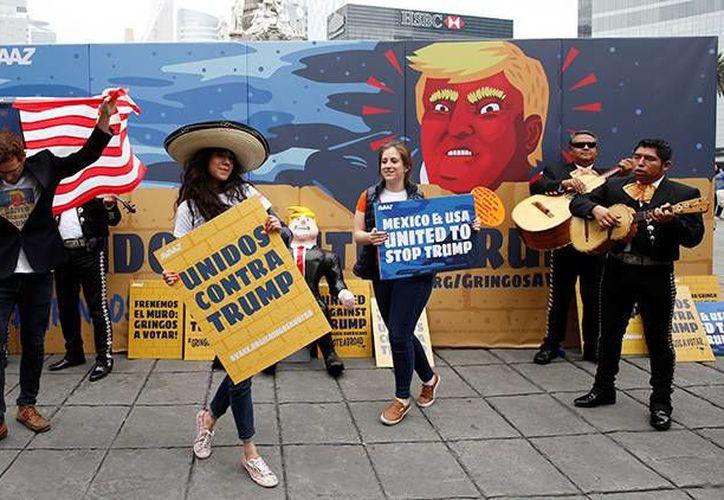 Un mariachi toca frente a un muro que tiene una caricatura de Donald Trump durante una campaña para promover el voto latino. (Carlos Jasso/Reuters)