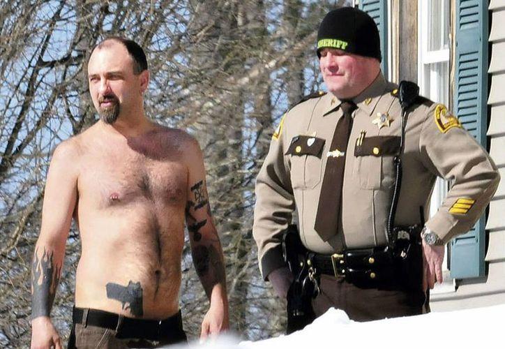 Michael Smith (izq.) exhibe un tatuaje realista de un pistola en su estómago mientras es acompañado por un policía del Condado Somerset afuera de su hogar en Norridgewock, Maine. (Foto AP/Morning Sentinel, David Leaming, archivo)
