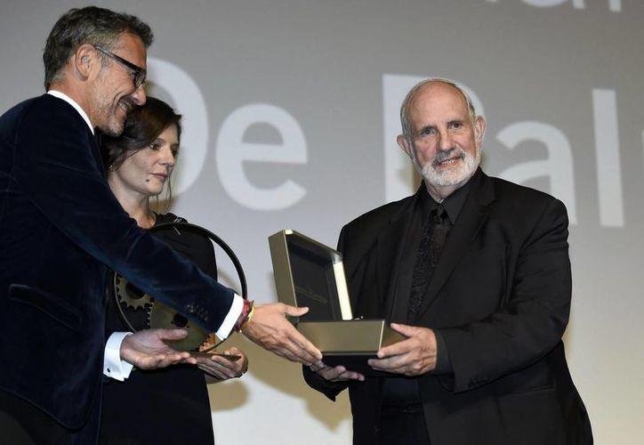 El director Brian De Palma (d) es galardonado por la actriz francesa Chiara Mastroianni (c) y el director de Comunicaciones de Jaeger-LeCoultre, Laurent Vinay (i) en la ceremonia del Premio Gloria al Realizador 2015 Jaeger-LeCoultre ayer, durante el Festival de Cine de Venecia. (EFE)