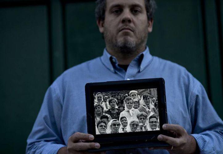 Pedro Sandoval, que fue robado cuando era bebé, posa con una imagen enmarcada del grupo Abuelas de la Plaza de Mayo, en la que aparecen sus dos abuelas, que le ayudaron a recuperar su verdadera identidad. (Agencias)