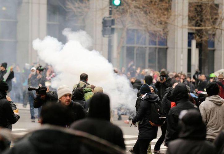Policías lanzan gas lacrimógeno a manifestantes que realizaron actos vandálicos en Washington, D.C., tras la toma de protesta de Donald Trump, el viernes 20 de enero de 2017. (Fotos: AP/Mark Tenally)
