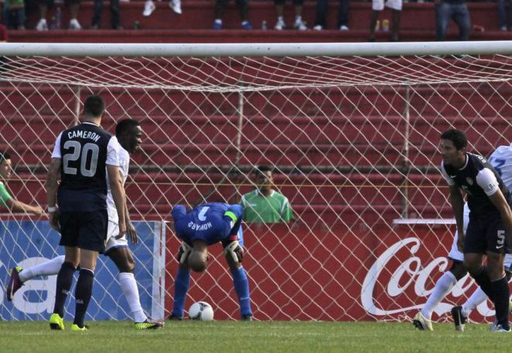 El arquero estadunidense Tim Howard (i) se enoja tras recibir un gol de chilena de García (d). (AP)