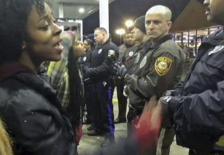 Captura de un video en el que se registró a varias personas al increpar a un grupo de agentes de policía, en Berkeley, Misuri, después de que un agente disparara y matara a un joven afroamericano. (EFE)