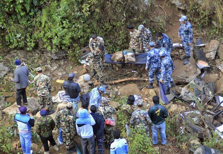 Personal de seguridad inspecciona el lugar donde se ha producido un accidente cerca de Chidipani, a unos 320 km de Katmandú, Nepal. (EFE)