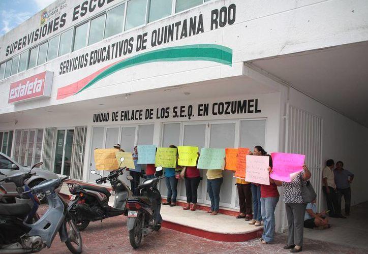 Los docentes se apostaron con pancartas en las oficinas de la SEyC. (Julián Miranda/SIPSE)
