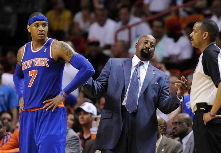Carmelo Anthony (i), de los Knicks, observa al oficial Adams (d), mientras el entrenador Mike Woodson (C) discute ante los Heat de Miami. (EFE)