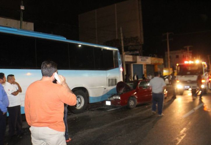 El chofer del Golf rojo y su acompañante quedaron prensados tras chocar contra un autobús estacionado. (Redacción/SIPSE)