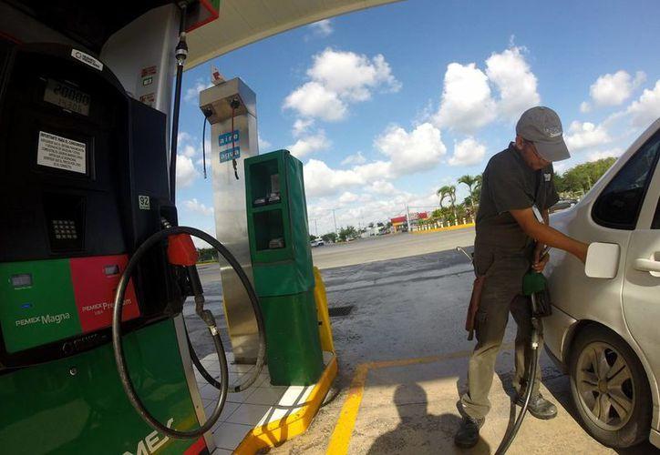 La SHCP va a postergar por segunda ocasión en lo que va del año el incremento en los precios de las gasolinas y se van a mantener en el mismo nivel al que se venden desde el 1 de enero, revelaron fuentes cercanas a la dependencia. Imagen de contexto de un empleado al momento de despachar gasolina a un vehículo. (Notimex)
