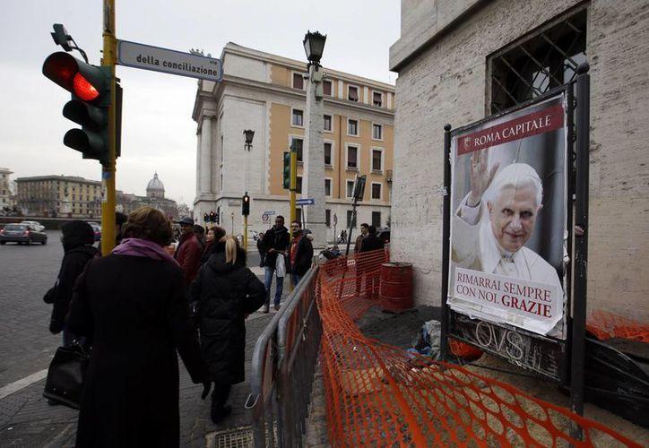 La gente pasa junto a un cartel del Papa Benedicto XVI. (Agencias)