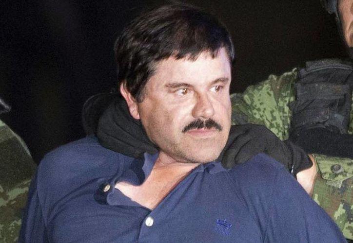 Imagen de El Chapo al momento de que elementos de la Marina lo suben a un helicóptero. Los acompañantes del capo en el momento del operativo fueron ingresados a penales de máxima seguridad. (AP Photo/Eduardo Verdugo)