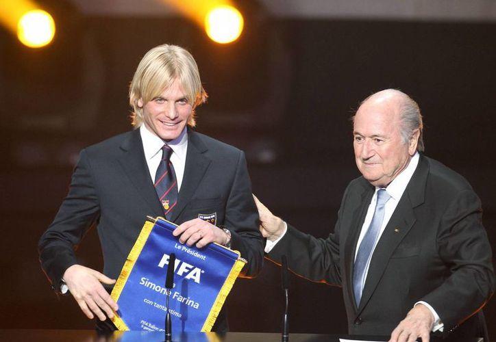 El defensa italiano Simone Farina, felicitado por Blatter (d) denunció un intento de soborno, que derivó en arrestos. Sus paisanos lo rechazaron por 'soplón'. (Agencias)