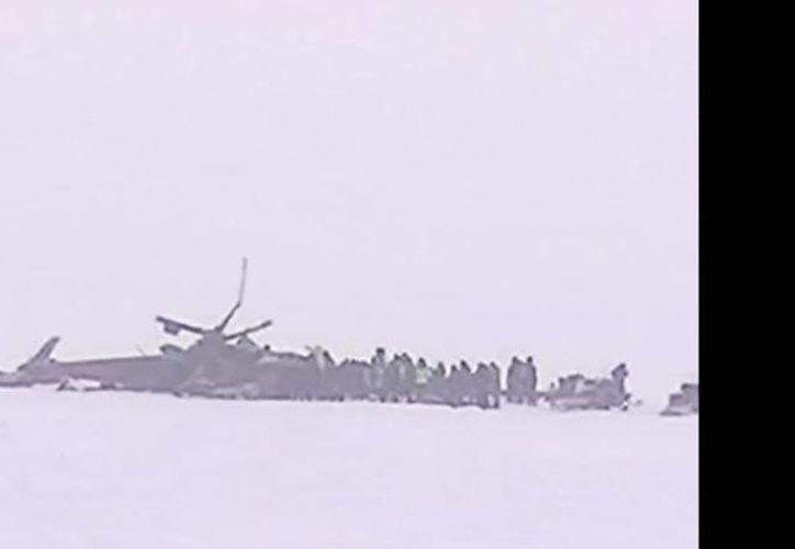 Captura de video del canal de YouTube de RT, la cual muestra los restos del helicóptero ruso que se estrelló en Siberia. (YouTube)