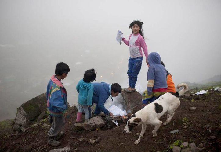 Un grupo de niños enciende una fogata en el barrio limeño Virgen de las Mercedes. La niebla impide ver la ciudad a sus pies.  (Agencias)