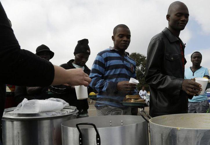 Un grupo de hombres hacen fila para pedir comida en un campamento de refugiados en Johannesburgo, donde están los extranjeros que huyen de sus países. Un total de siete personas han muerto en los ataques contra los inmigrantes en Sudáfrica. (AP)