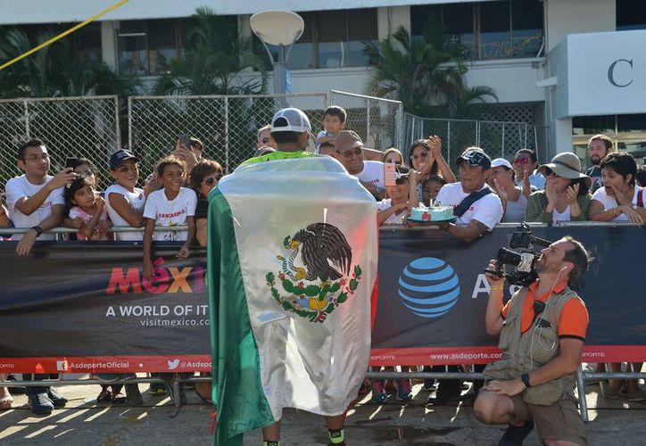 Envuelto en la Bandera de México, Alan Carrillo fue recibido en la meta como un héroe. (Gustavo Villegas/SIPSE)