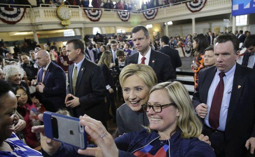 Hillary Clinton posa para una foto con una seguidora en un evento de campaña en Old South Meeting House, en Boston. (Agencias)