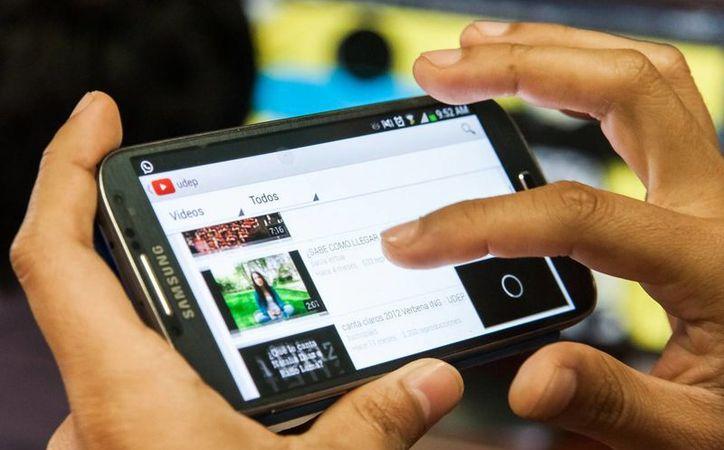 Actualmente la misa episcopal se graba y edita para Youtube. Imagen de contexto de una persona mientras usa el canal de videos en un celular. (Milenio Novedades)