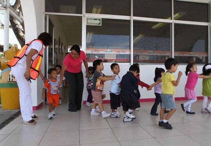 El personal de una guardería de Progreso aplicó el protocolo de seguridad y evacuó a unos 20 niños del plantel, tras dispararse las alarmas por una fuga gas en un predio vecino. La foto corresponde a un simulacro de incendio guardería de Chetumal, en 2013. (Novedades de Quintana Roo)