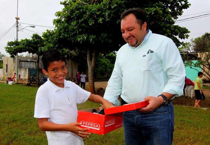 El diputado Francisco Torres entrega un para de tenis al niño Kenny Emanuel Cáceres Valle. (SIPSE)