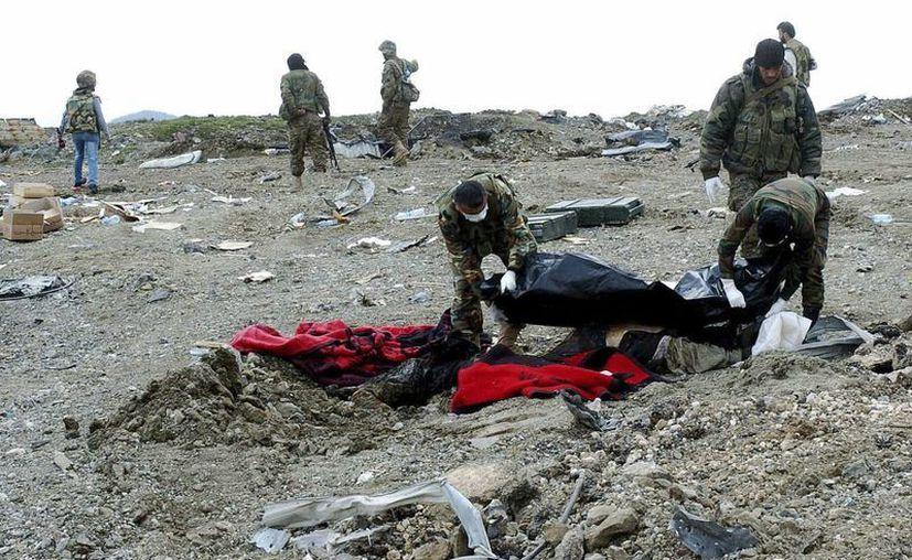 Fotografía cedida por la Agencia Siria de Noticias SANA que muestra a soldados sirios recogiendo cadáveres al finalizar la ofensiva rebelde en la provincia de Lattakia, Siria. (EFE)