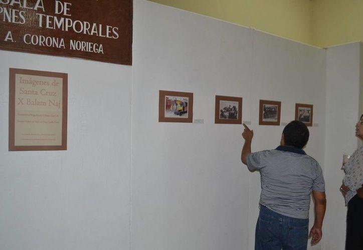 Los visitantes analizan las imágenes ubicando cada uno de los sitios a los que se hace referencia, en la muestra de la Casa de la Cultura. (Manuel Salazar/SIPSE)
