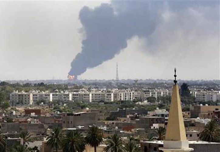Columnas de humo se elevan al cielo desde el depósito de petróleo del Aeropuerto de Trípoli, Libia, durante los combates entre milicianos islamistas y sectores leales al nuevo parlamento. (Agencias)