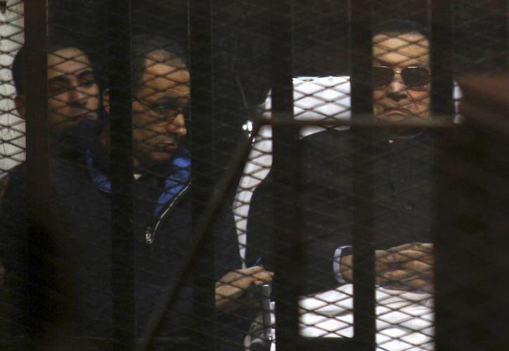 El expresidente egipcio Hosni Mubarak (d), de 86 años, aparece junto a uno de sus hijos, Gamal, durante el juicio en su contra por asesinato y corrupción, en el Cairo. (Foto: AP)