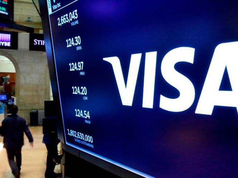 In this April 23, 2018, file photo, the logo for Visa appears above a trading post on the floor of the New York Stock Exchange.