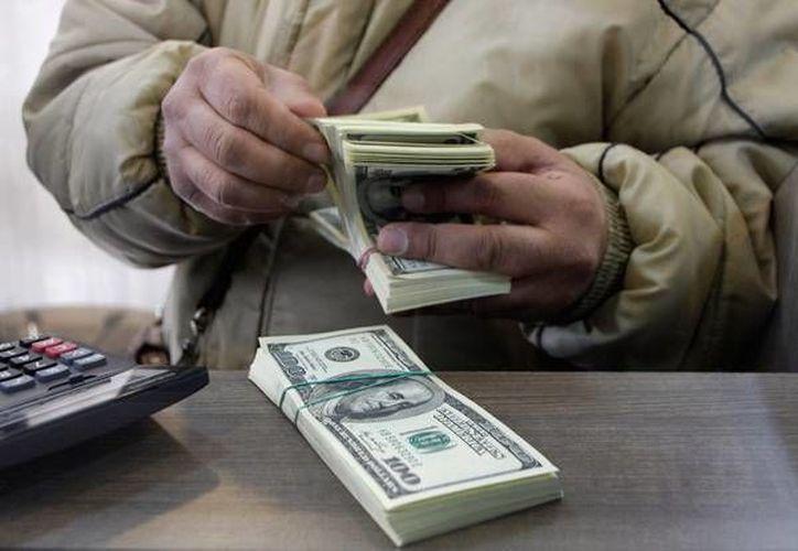 El dólar se compró en un mínimo de 14.02 pesos, en bancos del Distrito Federal. (Archivo/AP)