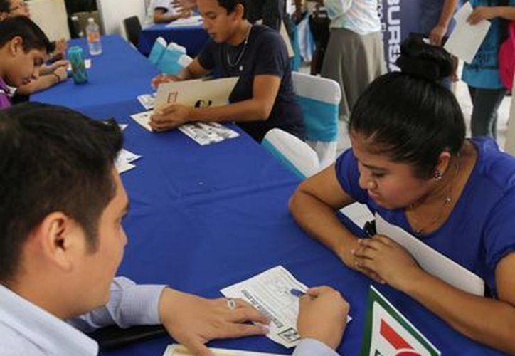 Jóvenes piden informes en una de las empresas que ofrecen vacantes en la Feria Juvenil del Empleo. (SIPSE)