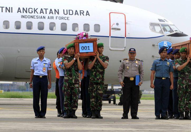 Soldados indonesios cargan los féretros de las primeras víctimas del vuelo 8501 de AirAsia, a su arribo a la base militar Surabaya, en Indonesia, este 31 de diciembre de 23014. (Foto: AP)
