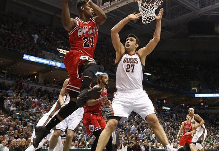 Jimmy Butler (21), de Bulls, avanza hacia la canasta pese a la cercanía de Zaza Pachulia (27), de Bucks, en el sexto y definitivo juego de la serie, que terminó 4-2 a favor de los astados. (Foto:AP)
