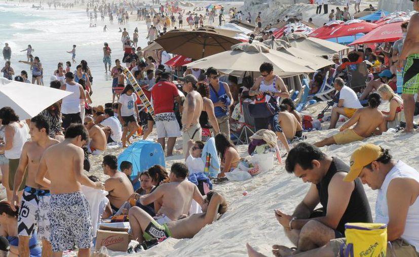 Algunos turistas no pudieron colocar sus sombrillas porque el espacio estaba lleno de camastros por los cuales cobraban. (Jesús Tijerina/SIPSE)