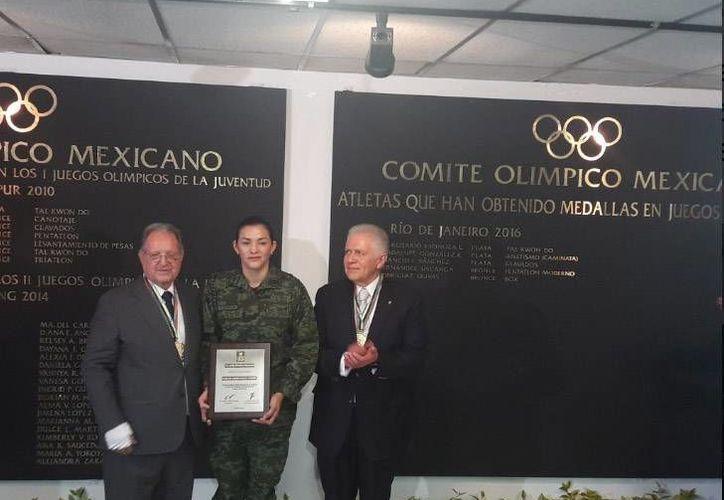 Olegario Vázquez (i) y Carlos Padilla entregaron reconocimientos a los cinco medallistas mexicanos  en Río 2016. En la foto, María del Rosario Espinosa recibe reconocimiento.(Foto tomada de Twitter/COM)
