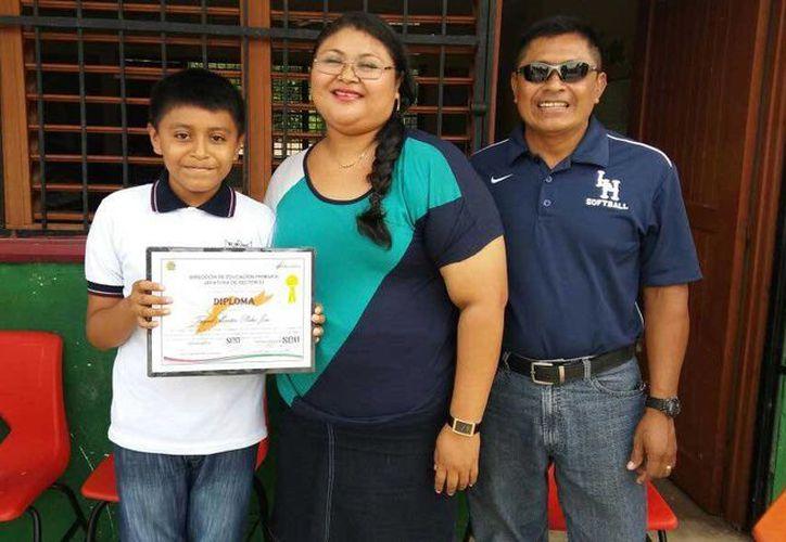Pedro José Tuyub Martín, posa con sus padres luego de haber conocido al presidente de México. (Tony Blanco/SIPSE)