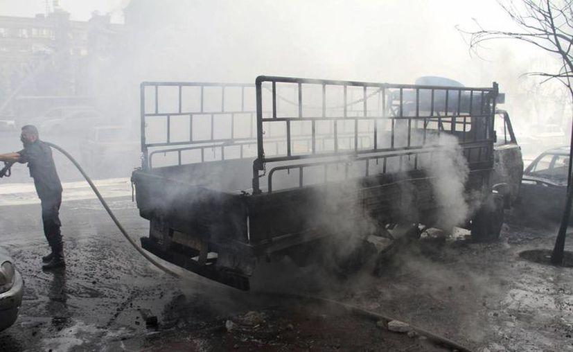 Un bombero apaga el fuego causado por la caída de dos bombas lanzadas con morteros cerca del orfanato de Dar al-Aman en Damasco. (EFE)
