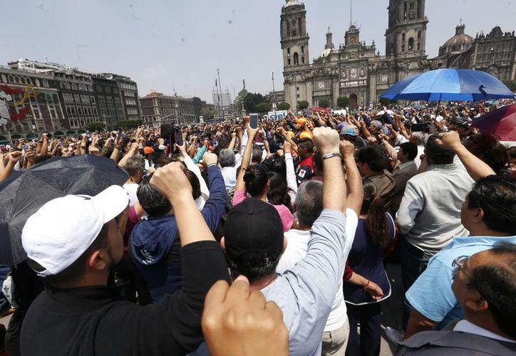 En el zócalo, decenas de personas se reunieron para conmemorar el primer aniversario del sismo del 19 de septiembre. (Milenio)