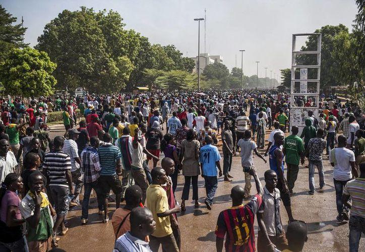 Centenares de manifestantes recorren las calles de Uagadugú, Burkina Faso, donde asaltaron e incendiaron el Parlamento en protesta por la votación de la enmienda constitucional impulsada por el jefe de estado para prolongar su mandato. (EFE)