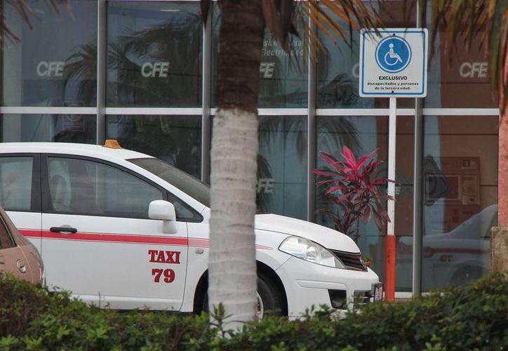 Taxistas se estacionan a esperar pasaje justo en los lugares asignados para personas especiales en el estacionamiento de un supermercado. (Gustavo Villegas/SIPSE)
