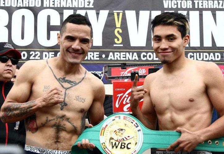'Vikingo' Terrazas y 'Rocky' Hernández posan con el cinturón que disputan este sábado en la Arena Coliseo de la Ciudad de México, durante el pesaje, el viernes 21 de octubre de 2016. (Notimex)