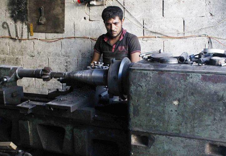 Un integrante de las tropas opositoras al régimen de Bachar al Asad durante el proceso de fabricación de bombas y la reparación de artillería en el barrio de Tareq Al-Bab, Alepo. Ofrecen un indulto a los rebeldes que entreguen sus armas (EFE/Archivo)