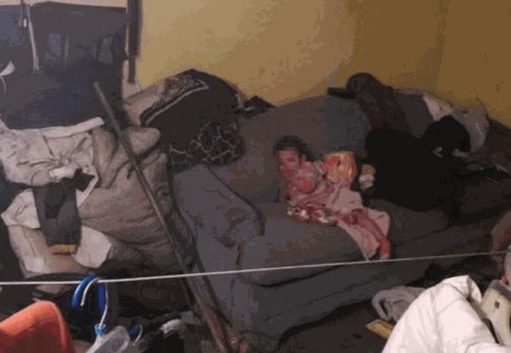 La menor estaba sentada en el sillón de su casa bajo ropa sucia y basura. ](Foto: La Silla Rota)