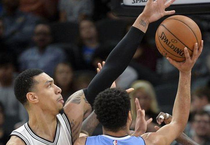 Danny Green (14), defensa de Spurs, bloquea el tiro de Jamal Murray, guardia de los Nuggets de Denver en partido ganado por los primeros. (AP)
