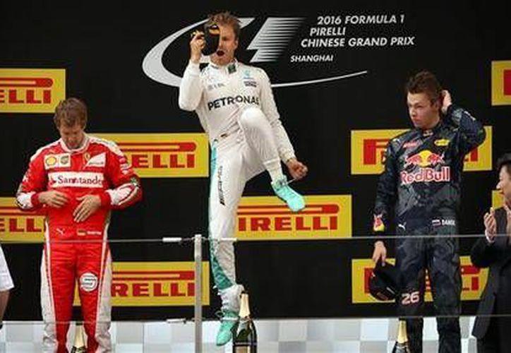 Nico Rosberg, de Mercedes Benz (centro) salta mientras celebra su victoria con Sebastian Vettel, de Ferrari a la izquierda, y Daniil Kvyat de Red Bull, a la derecha, en el Gran Premio de China de Fórmula 1. (AP)