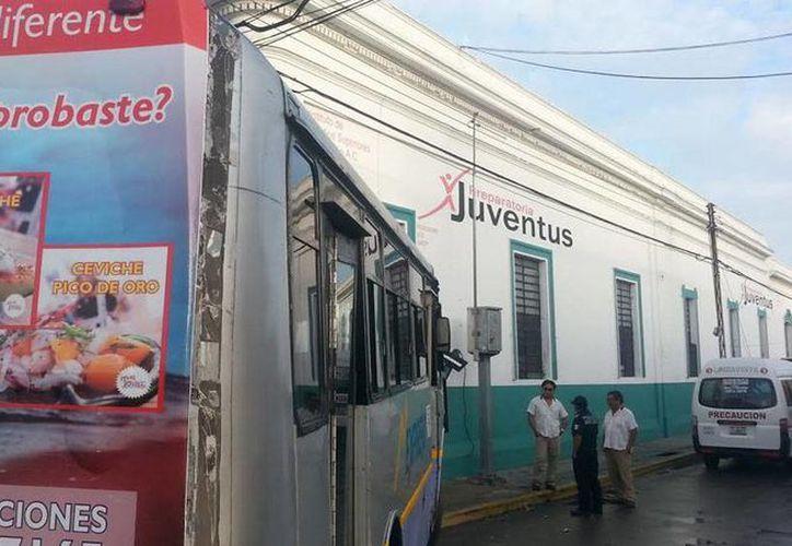 Todos los lesionados en el choque en pleno centro de Mérida viajaban en el taxi colectivo. El autobús terminó en la pared de una escuela. (SIPSE)