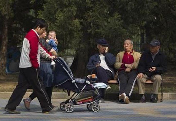 Unos ancianos descansan en una banca mientras una familia pasa caminando frente a ellos en un parque de Beijing, China. (Agencias)