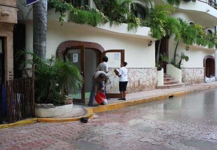 Empleados tenían que sacar el agua que entraba a los hoteles. (Loana Segovia/SIPSE)