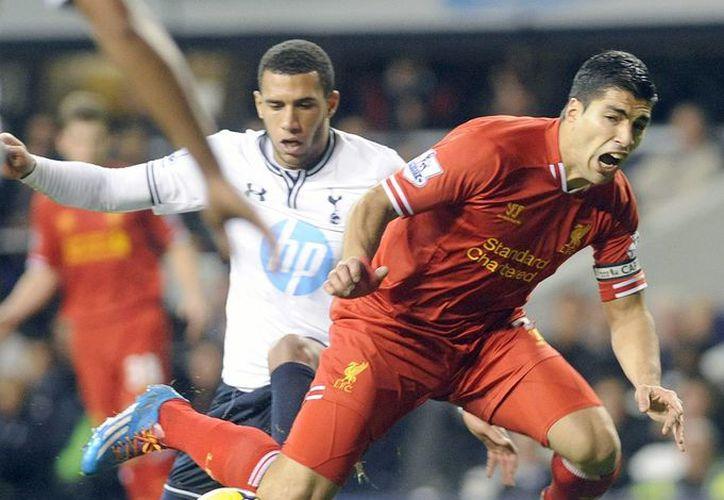 Suárez (de rojo), máximo goleador de la Liga Premier, con 17 tantos en 11 partidos, seguirá ligado al Liverpool. (EFE)